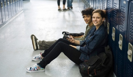 High school student sitting on floor with friend by lockers in school corridor